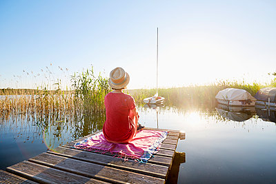 Frau auf einem Steg im Sonnenuntergang - p464m2203462 von Elektrons 08