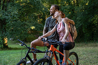 Smiling young couple sitting on bicycles in forest - p623m2294849 by Frederic Cirou