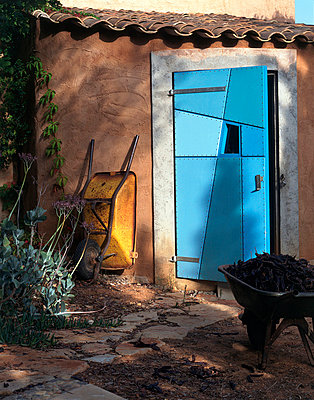 Yellow wheelbarrow outside quirky blue patchwork shed door - p8551887 by Richard Bryant