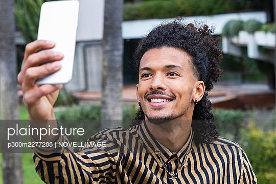 Smiling man taking selfie through smart phone - p300m2277288 by NOVELLIMAGE