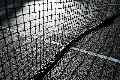 Tennis court with net and shadows - p1057m1502834 by Stephen Shepherd
