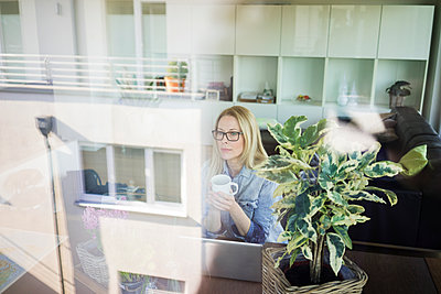 Mature businesswoman sitting at  table with cup of coffee looking out of window - p300m1587414 by Robijn Page