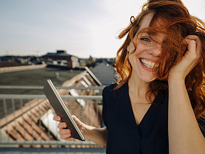 Portrait of happy redheaded woman with tablet on rooftop terrace - p300m2166661 von Kniel Synnatzschke