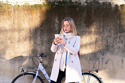 Female higher education student with bicycle looking at smartphone - p429m2091622 by Francesco Buttitta