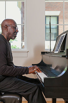 Man playing piano near window - p555m1303735 by Strauss/Curtis