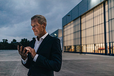 Businessman using smartphone at night - p586m1208535 by Kniel Synnatzschke