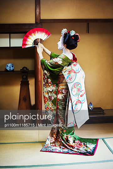 A woman dressed in the traditional geisha style, wearing a kimono and obi, with an elaborate hairstyle and floral hair clips, with white face makeup with bright red lips and dark eyes. Standing in a classic pose with fan raised, side view.  - p1100m1185715 by Mint Images