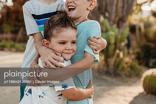 Close up of young toddler boy being hugged by older brothers - p1166m2136661 by Cavan Images