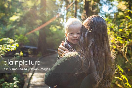 Happy boy looking over mothers shoulder. - p1166m2255414 by Cavan Images