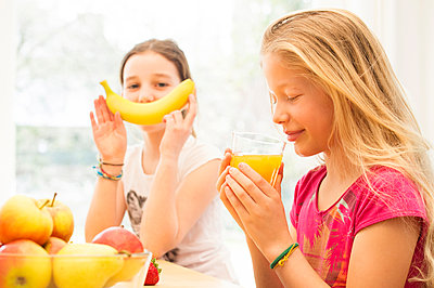 Portrait of girl drinking glass of orange juice while her friend having fun with banana - p300m1580927 by Nell Killius