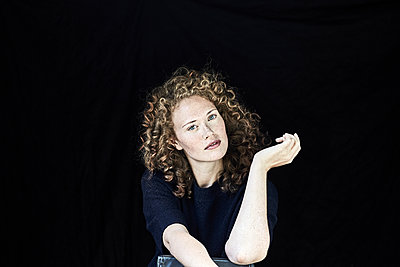 Portrait of young woman with curly  hair in front of black background - p300m2029035 by Jo Kirchherr