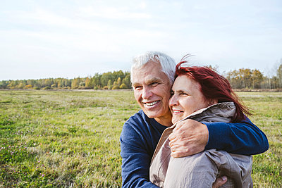 Happy senior couple embracing while looking away on field - p300m2225483 by Ekaterina Yakunina