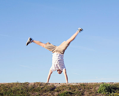 Mid adult man doing cartwheel in a park - p3741486 by Olli-Pekka Orpo
