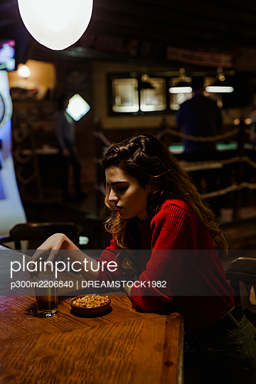Sad mid adult woman with alcohol and snacks on table sitting in restaurant - p300m2206840 by DREAMSTOCK1982