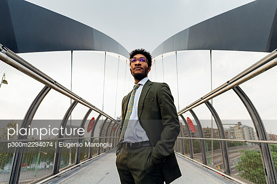 Confident businessman with hands in pockets standing on bridge - p300m2294074 by Eugenio Marongiu