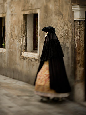 A person in carnival costume, a woman in a black cloak and dress with petticoats, wearing a white face mask and tricorn hat.  - p1100m991382f by Mint Images