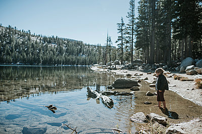 Side view of boy standing in lake during sunny day at Yosemite National Park - p1166m1526873 by Cavan Images