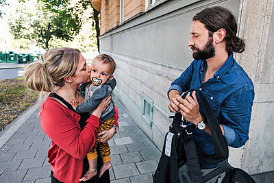 Working mother kissing baby boy while man holding carrier on sidewalk - p426m1108174f by Maskot