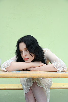 Sad young woman on a beer bench - p427m2203621 by Ralf Mohr