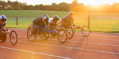 Determined paraplegic athletes speeding along sports track in wheelchair race - p1023m2067593 by Martin Barraud