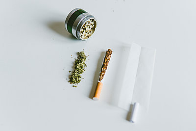 Overhead view of marijuana joints, cigarette with paper and grinder on white table - p1166m2001306 by Cavan Images