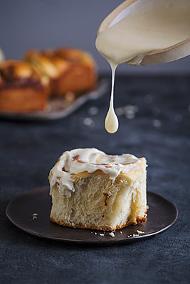 Close-up of cream pouring on cinnamon bun in plate on table - p1166m2067178 by Cavan Images