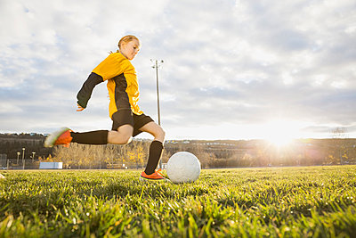 Soccer player kicking ball on field - p1192m1043880f by Hero Images