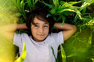 Smiling boy with hands behind head resting on grass in meadow - p300m2221732 by Valentina Barreto