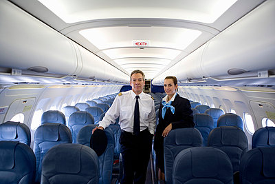 A pilot and a flight attendant standing in the cabin of a plane - p3018297f by Halfdark