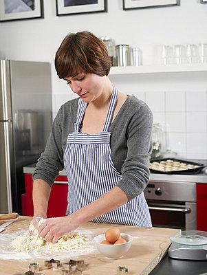 Junge Frau beim Plaetzchen backen  - p6430171f von senior images RF