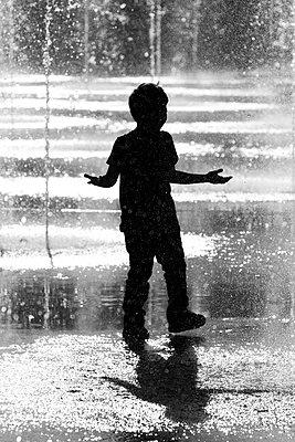 Junge spielt unter Springbrunnen - p977m1137383 von Sandrine Pic