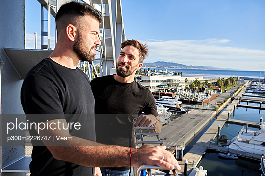 Gay couple on footbridge while Mediterranean Sea in background - p300m2226747 by Veam