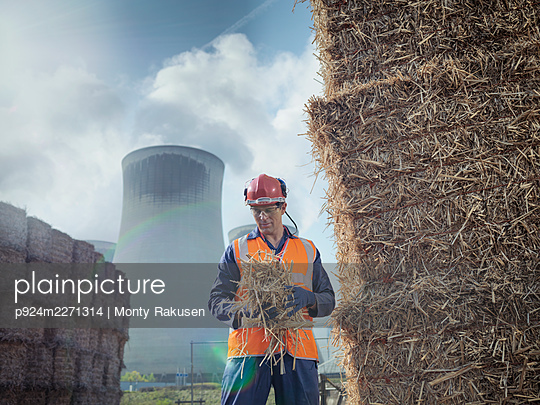 UK, North Yorkshire, Engineer at haystack in front of power station - p924m2271314 by Monty Rakusen