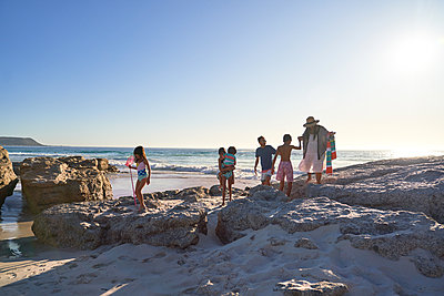 Family playing on rocks on sunny ocean beach, Cape Town, South Africa - p1023m2200860 by Trevor Adeline
