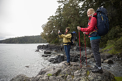 Active senior women friends backpacking on cliff overlooking ocean - p1192m2000416 by Hero Images