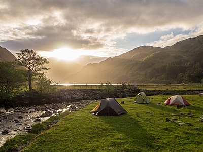 Tents on grassy land against cloudy sky during sunset, Scotland, UK - p300m2144117 by Hubertus Stumpf