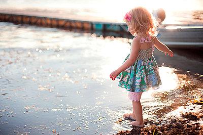 Girl dipping toe in rural lake - p555m1408928 by Shestock