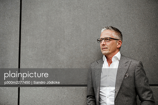 Serious male restaurant manager looking away - p300m2277450 by Sandro Jödicke