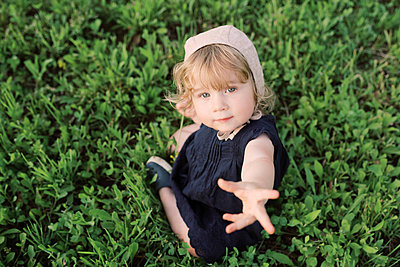 Little girl sitting in the grass. - p1166m2153914 by Cavan Images