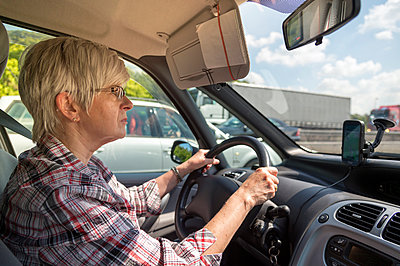 Germany, Brandenburg, senior woman driving car on motorway - p300m1028900f by Frank Röder