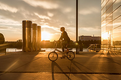 Senior woman riding city bike at the riverside at sunset - p300m2004107 by Jo Kirchherr