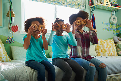 Black sisters holding donuts over eyes in bedroom - p555m1444149 by LWA/Dann Tardif