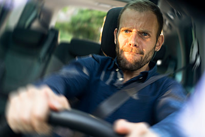 Frustrated young man driving a car - p623m2294862 by Frederic Cirou