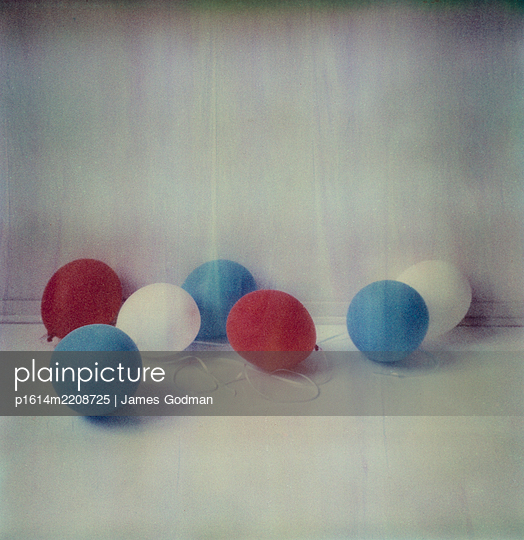 Deflated balloons on the floor - p1614m2208725 by James Godman
