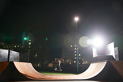 Young man skateboarding on ramp at skate park at night - p1023m2200954 by Himalayan Pics