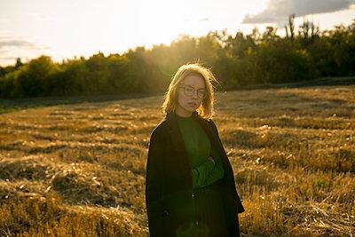Junge Frau auf einem Stoppelfeld in der Abendsonne - p1646m2249823 von Slava Chistyakov