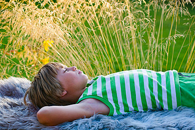 Boy sleeping on blanket outdoors - p312m695532 by Plattform photography