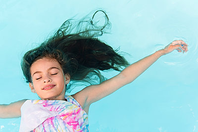 Smiling Caucasian girl floating in swimming pool - p555m1303496 by JGI/Jamie Grill