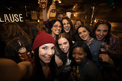 Portrait smiling women friends drinking beer at party - p1192m1403436 by Hero Images