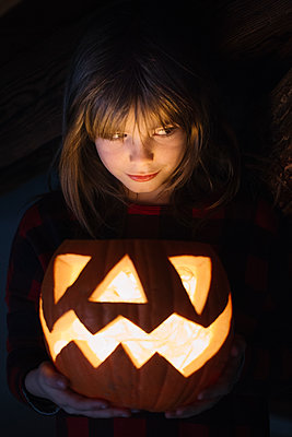 Portrait of girl with lighted Jack O'Lantern at Halloween - p300m1536024 by Alberto Bogo